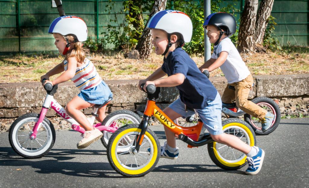 Gemeinsam lernt es sich besser! Das gilt für das Balancieren wie für das Helm tragen. Passen müssen sie natürlich, die Kopfschützer. Quelle/Source [´www.puky.de | pd-f´]